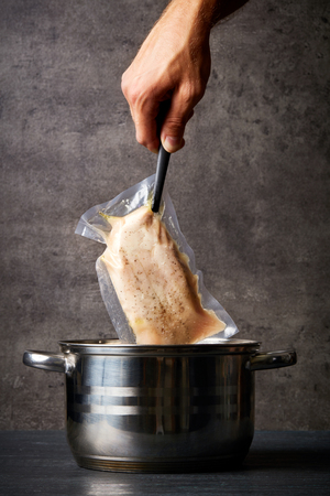 Hand holding chicken breast in sous vide bag over cooking pot