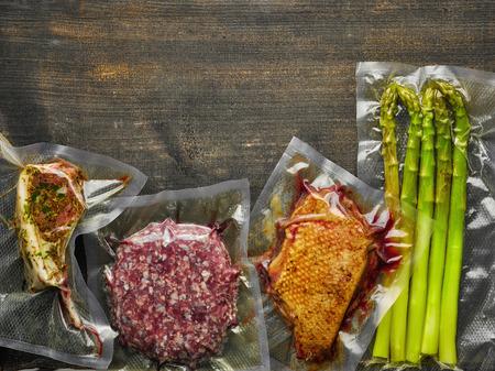 Fleisch und Spargel vakuumiert bereit zum Sous Vide Garen auf Holztisch, von oben