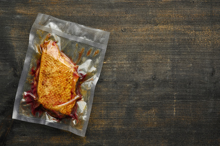 Duck breast vacuum sealed ready for sous vide cooking on wooden table, from above Stok Fotoğraf - 125534080