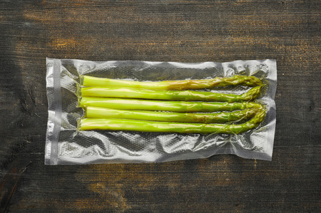 Asparagus vacuum sealed ready for sous vide cooking on wooden table, from above
