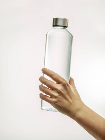 Hand holding reusable glass bottle with drinking water isolated on white background