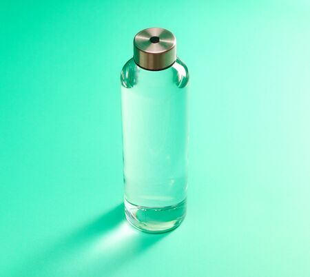 Reusable glass water bottle with stainless steel cap on mint green background