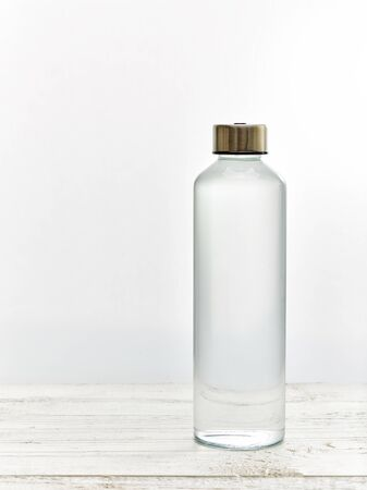 Reusable glass drinking water bottle on white wooden table