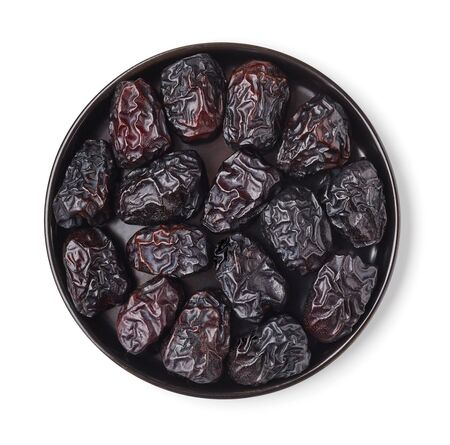 Black plate full of dates isolated on white background; top view Reklamní fotografie