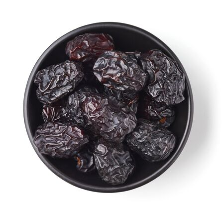 Black bowl of dates isolated on white background; top view