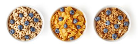 Three bowls of different cereals with fresh blueberries isolated on white background, top view Reklamní fotografie