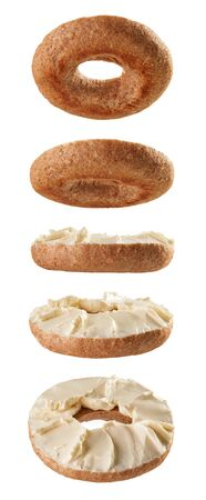 Halved bagel bottoms with cream cheese levitating in different positions isolated on white background Reklamní fotografie