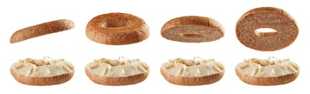 Halved fullgrain bagels with cream cheese levitating in different positions isolated on white background Reklamní fotografie