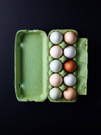 Fresh eggs from local farm in cardboard box on black background, top view