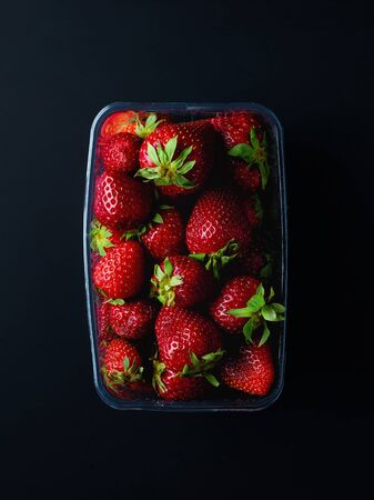 Strawberries in plastic transparent container box on black background, top view
