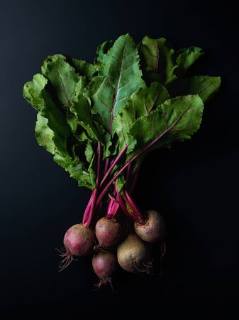 Bunch of fresh beetroots on black background, top view