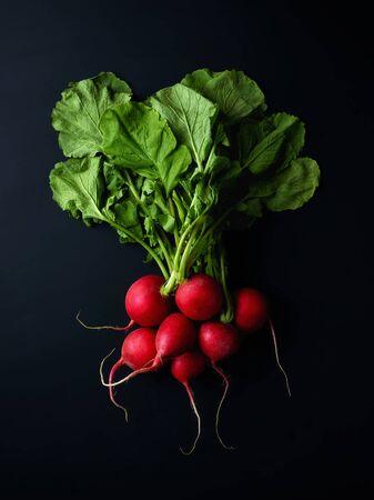 Bunch of fresh red radish on black background, top view Reklamní fotografie