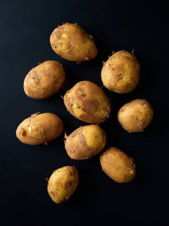 Heap of new potatoes on black background, top view