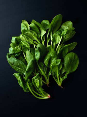 Heap of spinach leaves on black background, top view