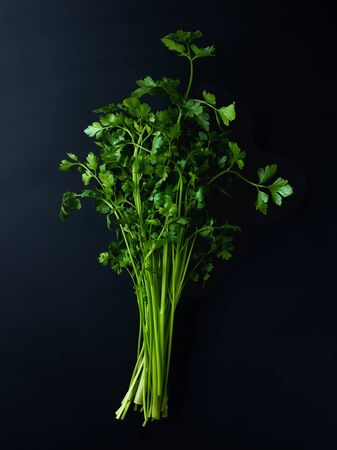 Bunch of fresh parsley on black background, top view