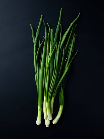 Bunch of fresh scallions on black background, top view Stock Photo