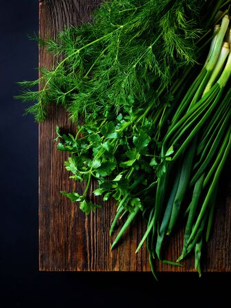 Bunch of fresh dill, parsley and scallions on wooden board ready for chopping on black background, top view
