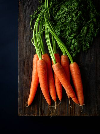 Bunch of fresh carrots on wooden board ready for chopping, black background, top view
