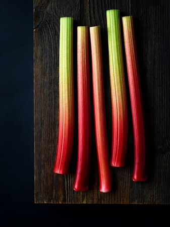 Fresh rhubarb stalks on wooden board ready for chopping, black background, top view