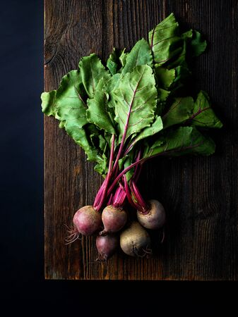 Bunch of fresh beetroots on wooden board ready for chopping, black background, top view