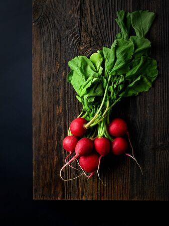 Bunch of fresh red radish on wooden board ready for chopping, black background, top view Reklamní fotografie