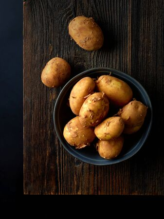 Bowl of new potatoes on wooden board ready for cooking, black background, top view