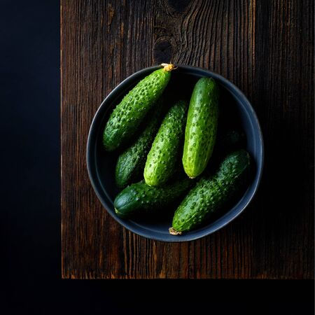 Bowl of short cucumbers on wooden table ready for chopping, black background, top view Reklamní fotografie