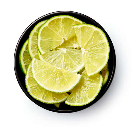 Black bowl of lime half slices isolated on white background, top view