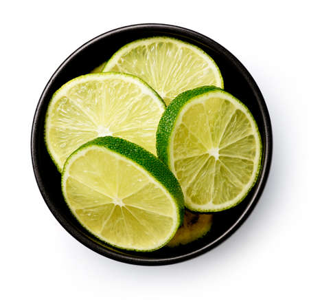 Black bowl of lime slices isolated on white background, top view 写真素材