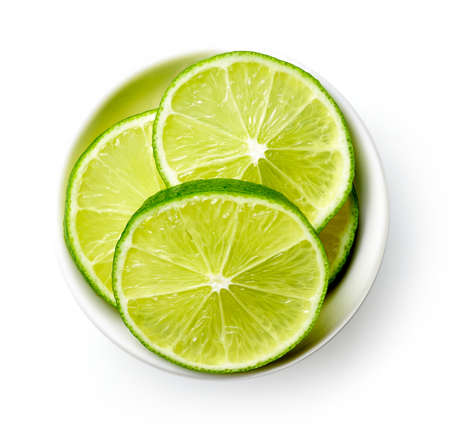 White bowl of lime slices isolated on white background, top view 写真素材