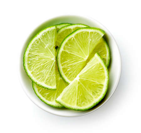 White bowl of lime half slices isolated on white background, top view 写真素材