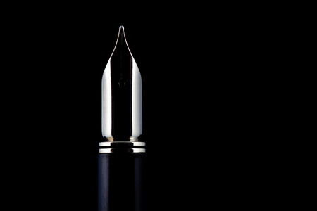 hand pen: Traditional Fountain Pen nib isolated against a black background.