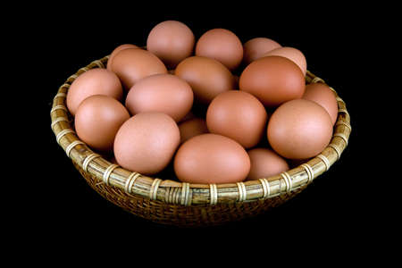 albumin: A whicker basket of fresh hens eggs isolated against a black background. Stock Photo