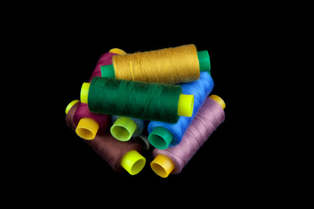 darn: Reels of colourful threads stacked against a black background.