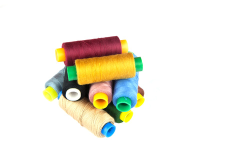 darn: Reels of colourful sewing threads stacked and isolated against a white background.