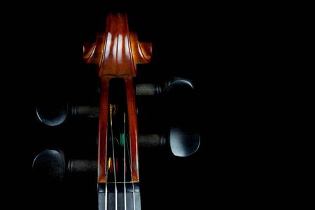 rosin: traditional violin scroll classically lit against a black background. Stock Photo