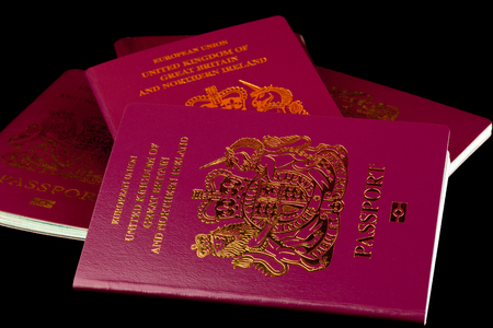 customs official: A stack of old and new UK passports isolated on a black background