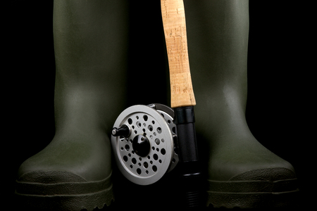 gum boots: Traditional fly fishing rod and reel with green rubber wading boots against a black background