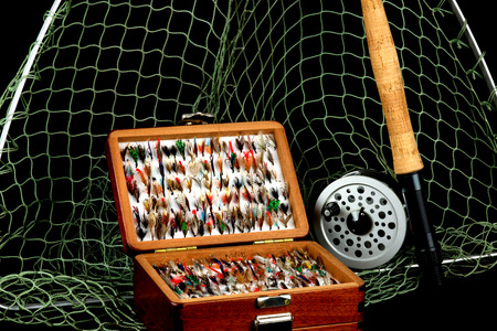 fly fish: Traditional Fly Fishing Rod Reel Net and Flies in Old Wooden Box Against a Black Background