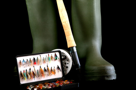 wading: Fly fishing rod and reel with green wading boots and fishing flies in flybox on black background Stock Photo