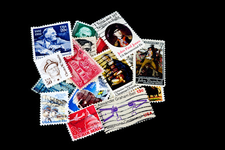 stamp collecting: A pile of assorted USA postage stamps isolated against a black background