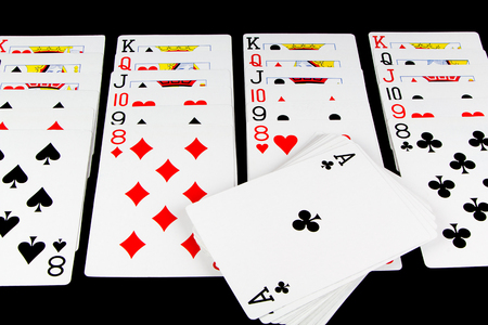 Playing cards being used for solitaire on black background Stock Photo
