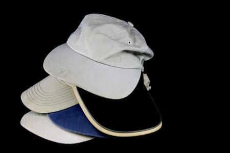 baseball caps: A pile of old worn baseball caps on black
