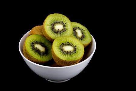 pith: A bowl of cut kiwi fruit isolated on a black background Stock Photo