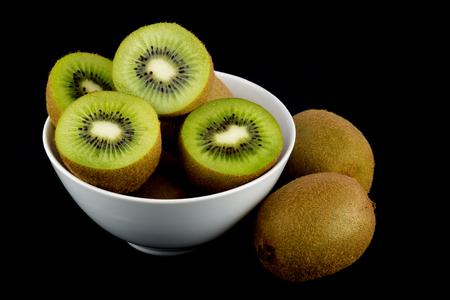 m�dula: Rodajas de kiwi y frutas enteras sobre un fondo negro