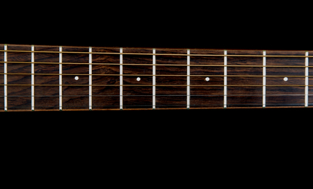 fretboard: Acoustic guitar neck and fretboard isolated against a black background Stock Photo
