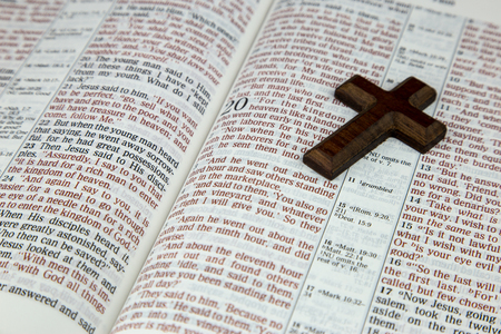new testament: An opened Bible and plain wooden cross