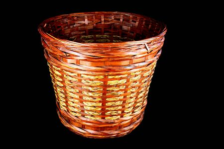 hand woven: A hand woven rattan waste paper basket isolated on black