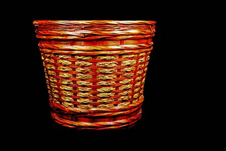 waste paper: Rattan waste paper basket isolated on a black background