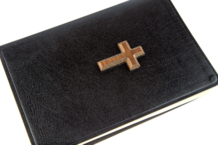 cross: A closed family bible and wooden cross on white background Stock Photo